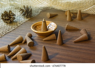 Incense aroma cones in a stand on a wooden table. Aromatherapy theme background.