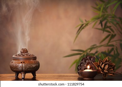 Incense burner and aromatic candle on table, Zen concept.