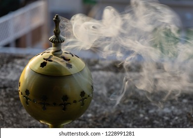 incense burner censer with smoke and blurred background.