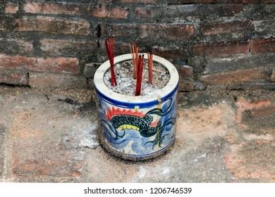an incense burner next to the old brick wall at the chinese shrine