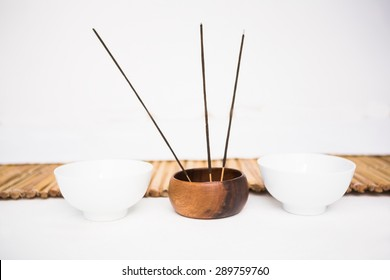 Incense burning and perfumed candles nearby a bamboo mat