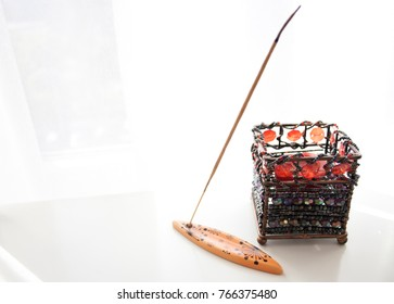 Incense with candlestick in front of white background