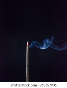 Incense stick are burning on the black background. The smoke of incense