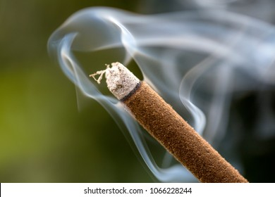 Incense stick burning with smoke, close up, macro. Island Bali, Ubud, Indonesia