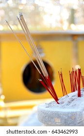 Incense stick in sand pot with yellow background