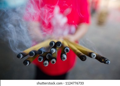 Incense sticks burning Embossed in hand. There is a lot of smoke. background blur man