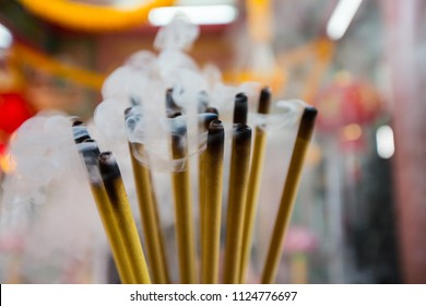 Incense Sticks burning Embossed in an incense pot. There is a lot of smoke. background chinese temple