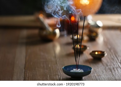 Incense sticks smoldering on wooden table in room. Space for text