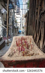 Incense sticks stand in a sidewalk shrine on a city street in Hong Kong
