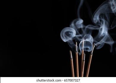 Incense sticks and incense stick smoke on black backgrond with white backlit