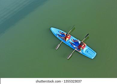 Inchathotty, Kerala, India - January 26, 2019: Male tourists enjoy kayaking in the tranquil backwaters of Periyar river at Inchathotty in Kerala, India.