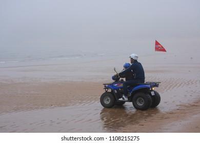 Incheon, Korea. May. 13, 2018 : A father and son riding a four-wheel bike on the beach in Korea.(Eulsang-ri Beach)