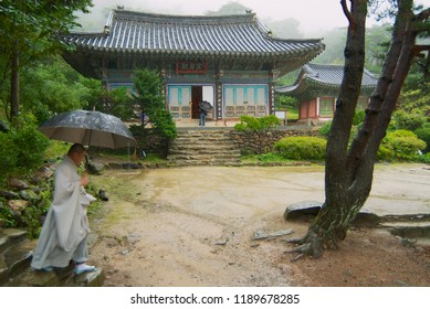Incheon, Korea - September 01, 2008: Monk walks by the Jeondeungsa temple territory on a rainy day in Incheon, Korea.