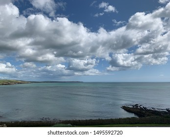 Inchydoney, Cork, Ireland - August 2019; View overlooking Inchydoney and Ring Head from Dunmore, with rocks and cliffs meeting calm ocean waters, blue sky and clouds above. - Shutterstock ID 1495592720