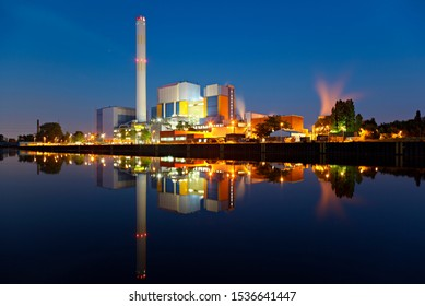 An incineration plant at a canal at blue hour in the night. Strong colors and very clear reflection.