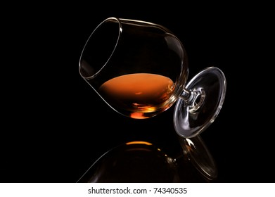 Inclined glass of cognac on black background