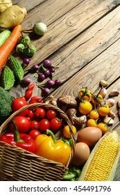 Include fresh organic vegetables in basket on wooden floor with copy space still life