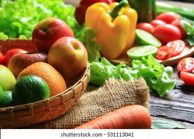 Include fresh organic vegetables basket on wooden floor with copy space still life