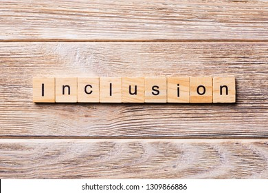 Inclusion word written on wood block. Inclusion text on wooden table for your desing, concept.
