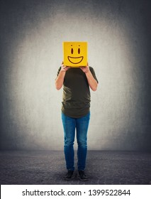 Incognito person holding a yellow box instead head. Introvert anonymous hiding face behind mask. Social issue fake identity concept, covering face with a positive smile emoticon.