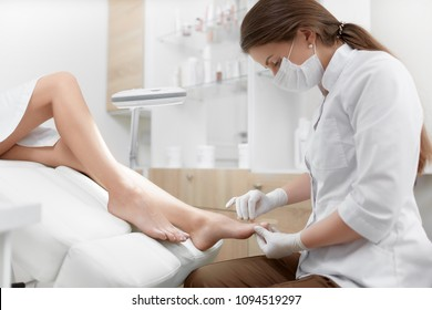 Incognito woman with perfect body caring about her foot and relaxing at beauty salon in arm chair. Brunette female podiatrist making polish and cleaning procedure for nails on foot with special tools.