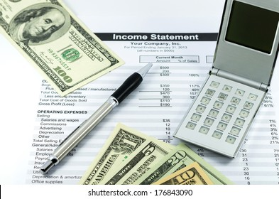 income statement report with calculator, pen and usd money for business
