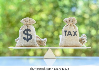 Income tax collection, strategy for paying tax, financial concept : Tax, dollar money bags on a simple / basic balance scale, depicts planning for reducing tax liability e.g investment and retirement