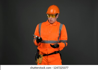 Incompetent newbie builder worker puzzled looks at the hammer in his hands isolated on gray background.