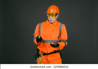 Incompetent newbie builder worker puzzled looks at the hammer in his hands isolated on gray background. Construction accident.