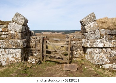 An incomplete broken stone arch through Hadrian's Wall as an entrance to the Northumberland landscape beyond