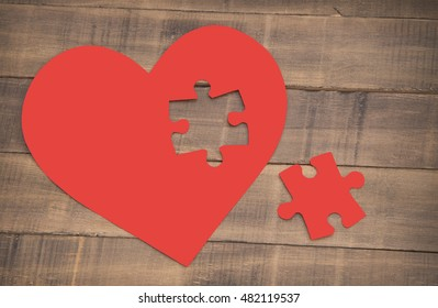 Incomplete puzzle in the shape of a heart on the wooden background