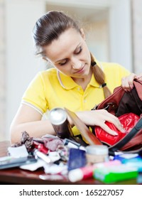 inconsiderate woman searching something in handbag at home