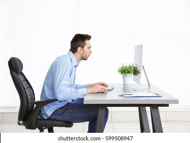 Incorrect posture concept. Man sitting at office table