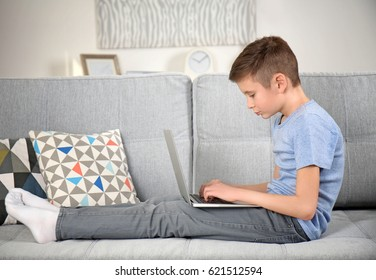 Incorrect posture concept. Schoolboy with laptop sitting on sofa