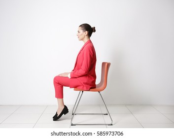 Incorrect posture concept. Young woman sitting on chair against white wall background