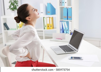 Incorrect posture concept. Young woman with back pain sitting at table in modern room