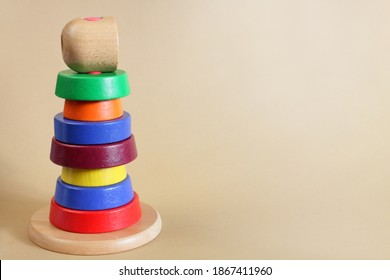 Incorrectly assembled pyramid toy. Wooden pyramid with colored rings on beige background. Kids toy for babies and toddlers to learn colors. The concept of disharmony or loss of form.