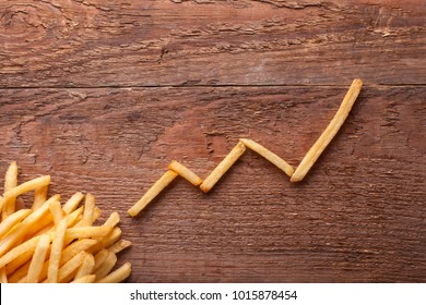 The increase in sales of food, the level of cholesterol is growing. French fries in paper packing and a chart up on a wooden table