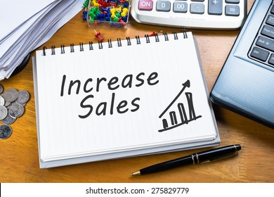 Increase Sales on notebook with part of laptop, receipts and calculator
