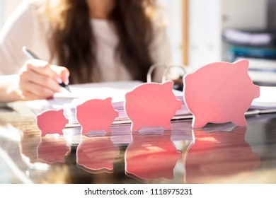 Increasing Flat Piggybank In Front Of Businessperson Working In Office