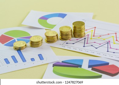 Increasing in size stacks of gold coins and colored graphics on a yellow background. Preparation of the report to investors on the financial condition. Concept