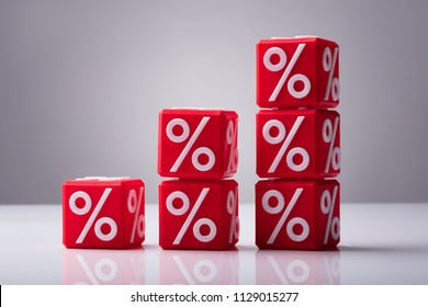 Increasing Stacked Red Cubes With Percentage Symbol Showing Upward Direction