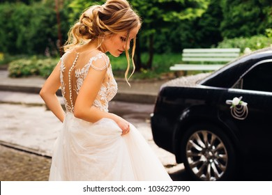incredible bride in white wedding dress and with a beautiful hairstyle goes to decorated black car