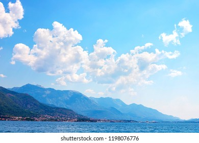 Incredible bright seascape. View of green wooded mountains and blue sea, blue sky and white clouds. Boka Kotorska Bay, Montenegro