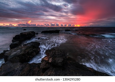 An incredible dramatic and beautiful sunset over the sea taken from above a rocky shore with beautiful white waves after a rain storm in Bali, Indonesia
