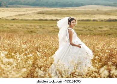 incredible and happy bride walking in a yellow field