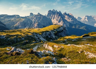 Incredible landscape with high mountains with illuminated peaks, reflection, blue sky and yellow sunlight in sunrise. Dolomites Alps. Amazing natural scene with Alpine Highlands During sunset.