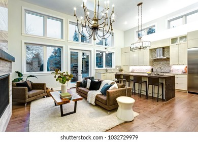 Incredible light and airy living room with high ceiling, Stone fireplace , large windows and stylish kitchen.
