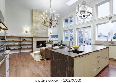 Incredible light and airy living room with high ceiling, Stone fireplace and large windows, view from stylish kitchen with granite top island.
