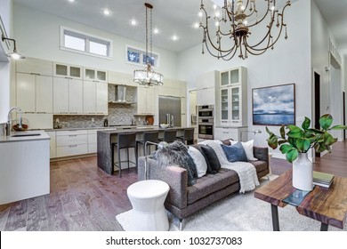 Incredible light and airy living room with high ceiling in a new construction home. Stone fireplace and large windows create cozy atmosphere.
